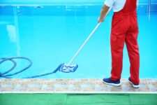 Male worker cleaning outdoor pool with underwater vacuum