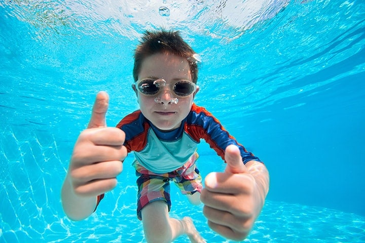 Young boy swimming underwater and giving two thumbs up for the camera