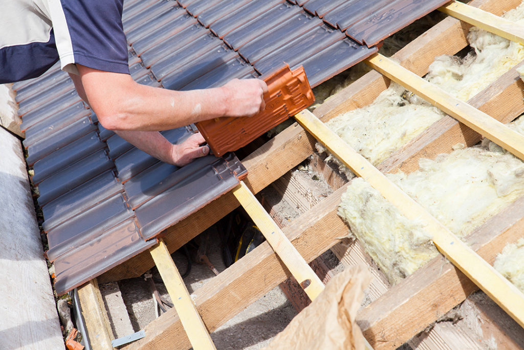 Roofer laying tile on the roof of a home