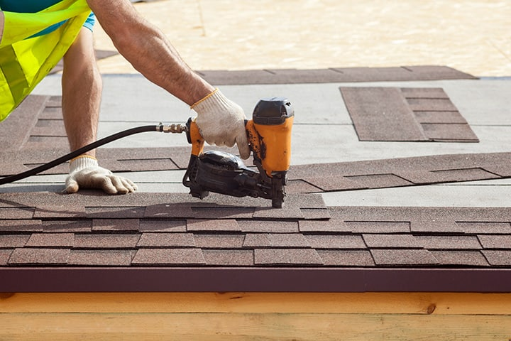 Roofer working on nailing down asphalt tiles instead of worrying about customer reviews