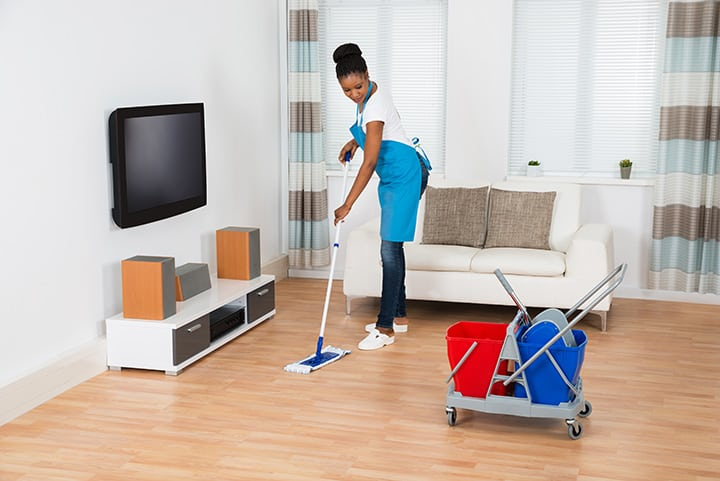 Home cleaning service business operator mopping a house